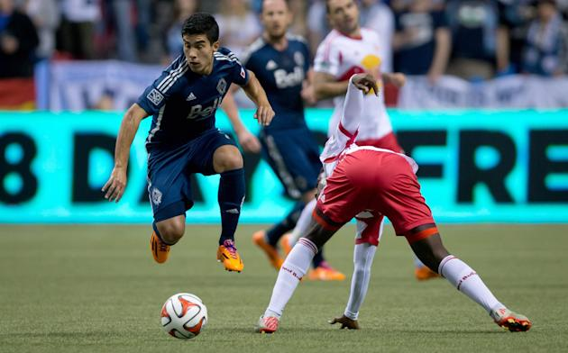 Vancouver Whitecaps' Sebastian Fernandez, left, of Uruguay, avoids the tackle from New York Red Bulls' Peguy Luyindula, of France, during first half MLS soccer game action in Vancouver, B.C.,