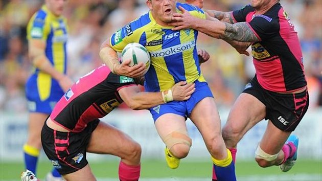 Warrington Wolves' Ben Westwood is tackled by Leeds Rhinos Jamie Peacock (right) and Carl Ablett during the Super League match at the Halliwell Jones Stadium, Warrington.
