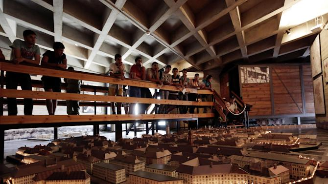 "Israeli high school students look at a model of the Warsaw Ghetto at the museum ""From Holocaust to Revival"" in Kibbutz Yad Mordechai near the costal town of Ashkelon, Sunday, April 7, 2013. The annual Israeli memorial day for the 6 million Jews killed during the Holocaust of the World War II begins at sundown Sunday. (AP Photo/Tsafrir Abayov)"