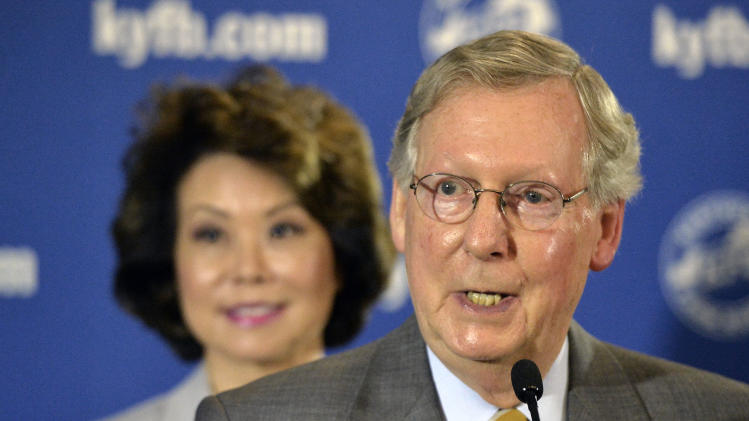 "This Aug. 20, 2014, file photo shows Senate Minority Leader Mitch McConnell of Ky., joined by his wife Elaine Chao, as he speaks to reporters following a candidates forum at the Kentucky Farm Bureau Insurance headquarters, in Louisville, Ky. The first midterm elections since both parties embraced a historic change in campaign finance, and with it a sea of campaign cash, will mean for most voters an avalanche of television ads trying to reach the few able to be swayed and willing to vote. In the nation's closest races for U.S. Senate, that translates into ""price per vote"" that could easily double what was spent in the 2012 presidential election. (AP Photo/Timothy D. Easley, File)"