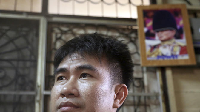 """In this photo taken Sept. 10, 2013, Thanawat Martnok poses for photographer with the photo of King Bhumibol Adulyadej, top, displayed at his house in Bangkok, Thailand. After having quarreled with his younger brother Yuthapoom Martnok, Thanawat told police that Yuthapoom had defamed King Bhumibol, an accusation that should be punished up to 15 years behind bars. Yuthapoom was indicted on charges of """"lese majeste"""" - insulting the royal family. Denied bail on national security grounds, he has been jailed for a year in a Bangkok prison where he is anxiously awaiting the court's verdict Friday, Sept. 13, 2013. (AP Photo/Apichart Weerawong)"""