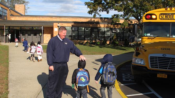 Bethpage Superintendent of Schools Terrence Clark welcomes back students to classes at Kramer Avenue Elementary School in Plainview, N.Y., on Monday, Nov. 5, 2012. The school was one of the first on Long Island to open after being closed for a week because of Superstorm Sandy.(AP Photo/Frank Eltman)