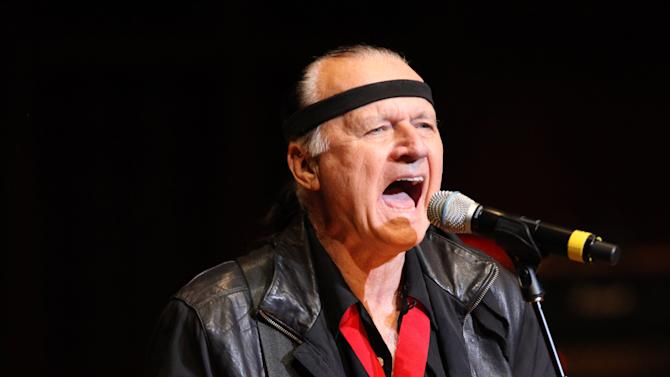 """FILE - This Oct. 12,2009 file photo shows Dick Dale performing in Nashville, Tenn. The son and ex-wife of 1960s """"King of the Surf Guitar"""" Dale were arrested after they allegedly blew up a propane tank in a Southern California desert town. Jill Monsour, 45, and James Monsour, 20, were arrested on suspicion of possessing an explosive device in public. (AP Photo/Josh Anderson,FILE)"""