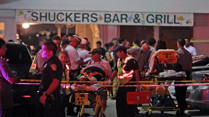 Rescuers transport an injured patron after a packed outdoor deck collapsed at a popular Miami-area sports bar Thursday June 13, 2013. Lt. Ignatius Carroll of Miami Fire-Rescue said late Thursday that 100 people fell into the water. He said rescuers pulled patrons from the bay, and that divers were searching waters underneath the collapsed deck as helicopters shined spotlights onto the area. (AP Photo/Miami Herald, Walter Michot)