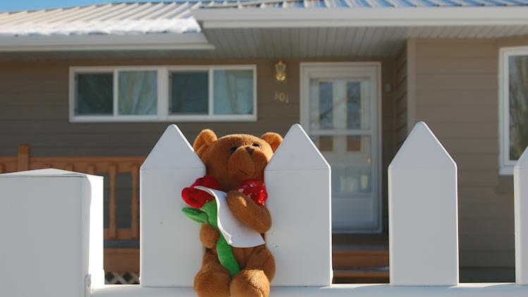 A stuffed bear is placed on a white picket fence on Monday, Nov. 19, 2012 in New Town, N.D. Authorities say  a woman and her three grandchildren were murdered in in the home on Sunday, Nov. 18, 2012. (AP Photo/James MacPherson)