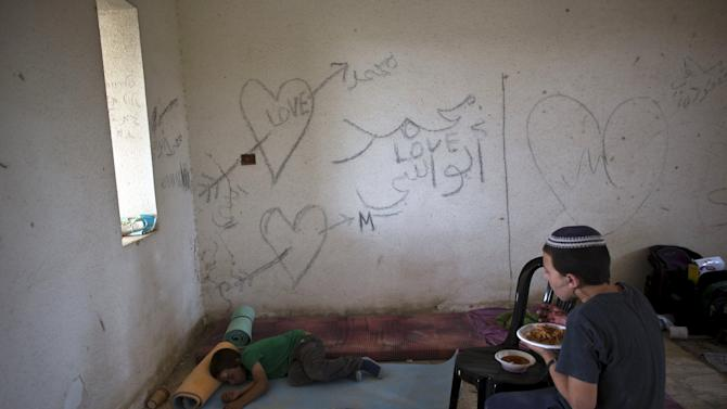 A boy eats as another rests on the floor inside an abandoned building at the evacuated settlement of Sa-Nur in the West Bank