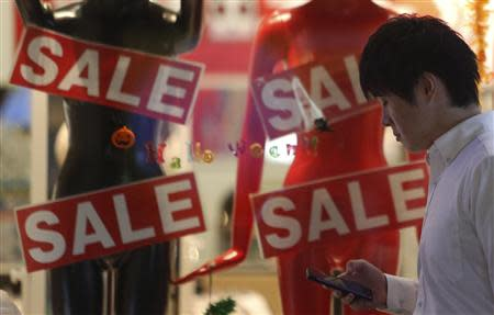 Man using smart phone walks past a retail shop advertising a sale, in Tokyo