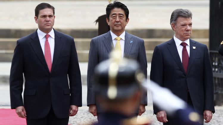 Japan's Prime Minister Abe, Colombia's President Santos and Colombia's Defence Minister Pinzon review the honour guard at the presidential palace in Bogota City