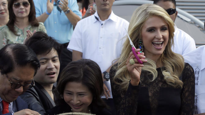 Paris Hilton, right, waves a pair of scissors after cutting the ribbon in the ceremony to unveil the Paris Beach Club, which she designed in collaboration with Philippine developer Century Properties, Thursday, March 13, 2014 at suburban Paranaque city, southeast of Manila, Philippines. Paris Hilton unveiled her first real estate project Thursday in metropolitan Manila and said she wants to follow in the footsteps of her great-grandfather and grandfather, who led a luxury hotel empire. (AP Photo/Bullit Marquez)