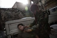 A Syrian rebel fighter cuts the beard of his companion in the center of Syria&#39;s northern city of Aleppo on October 24. Syria&#39;s army and main rebel force said they will cease fire on Friday, in line with an internationally backed truce during a Muslim holiday, but both reserved the right to respond to any aggression