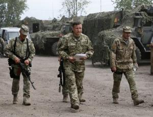 Ukrainian Defence Minister Heletey walks with troops at a temporary base nearSlaviansk