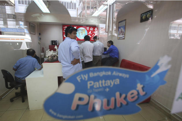 Policemen talk to a staff member of Grand Horizon Travel during questioning at its office in Pattaya, Chonburi province, Thailand, Monday, March 10, 2014. Thai police said owners of the travel agency