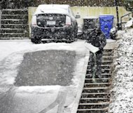 A man pours de-icing salts on the staircase in front of his Falls Church, Va., home in the falling snow, Wednesday, March 6, 2013. After pummeling the nation's midsection with heavy snow, a late-winter storm made its way Wednesday to the nation's capital, where residents braced for the possibility of power outages. As the storm closed in, the federal government said its offices in the Washington, D.C., area would be closed Wednesday. Many major school systems around Washington and Baltimore announced pre-emptive closures as well. (AP Photo/Cliff Owen)