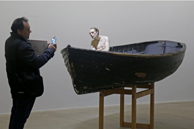 "A visitor shoots a sculpture entitled ""Man in a Boat"" by artist Ron Mueck during his exhibition at the Fondation Cartier pour l'art contemporain in Paris"