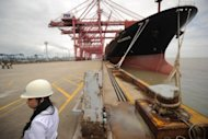 A worker at the Ningbo port stands beside a container ship wating to be loaded, June 2012. China said it has approved a package of measures aimed at boosting exports, as the world's second largest economy grapples with a slowdown