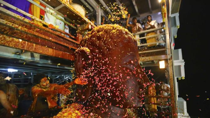 Devotees shower flowers on the 42-ft-tall monolithic statue of Lord Bahubali during the head-anointing ceremony of the Jain god in Karkala