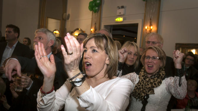Supporters of the Progressive Party celebrate while watching general election returns on a television, on Saturday, April 27, 2013, in Reykjavik, Iceland. Five years after Iceland's economic collapse, early returns signaled that voters are favoring the return of a center-right, Eurosceptic government, widely blamed for the nation's financial woes. (AP Photo/Brynjar Gauti)