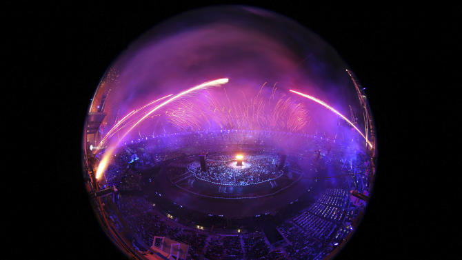 In a photo taken with a fisheye lens fireworks explode over the stadium at the end of the Opening Ceremony of the 2012 Olympic Summer Games at the Olympic Stadium in London, Saturday, July 28, 2012. (AP Photo/ Ezra Shaw, Pool)