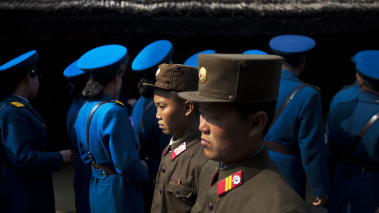 In this April 13, 2011 photo, North Korean soldiers, foreground, and North Korean traffic police, background, tour the birthplace of Kim Il Sung to pay their respects at Mangyongdae, North Korea. (AP Photo/David Guttenfelder)