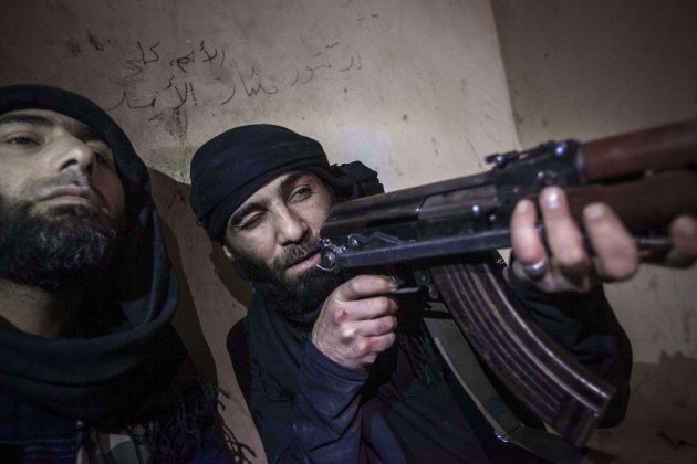 In this Wednesday, Dec. 5, 2012 photo, a Free Syrian Army fighter aims his weapon during heavy clashes with government forces in Aleppo, Syria. (AP Photo/Narciso Contreras)