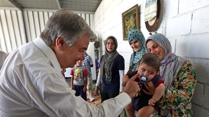 United Nations High Commissioner for Refugees (UNHCR) Antonio Guterres greets a Syrian child during his visit to Khaldeh, south of Beirut, Lebanon, Thursday, June 19, 2014. Guterres is visiting Lebanon where he will meet some Syrian refugees and discuss the situation with Lebanese officials. Lebanon, home to 4.5 million people, is struggling to cope with the presence of more than 1 million refugees in desperate need of housing, education and medical care. (AP Photo/Bilal Hussein)