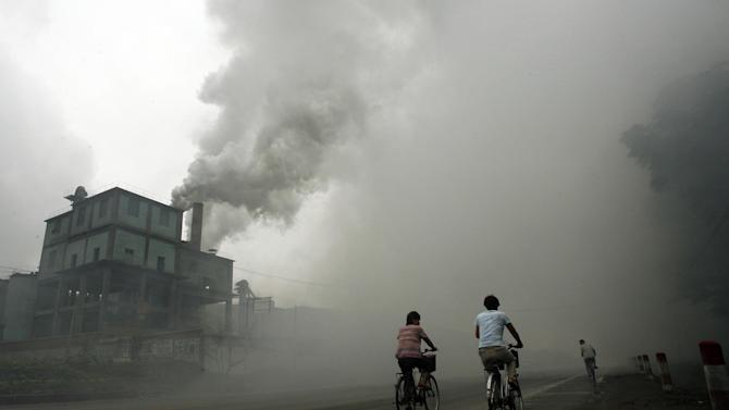 Cyclists pass through thick cloud of pollution from a factory in Yutian, east of Beijing, in China's northwest Hebei province, on July 18, 2006