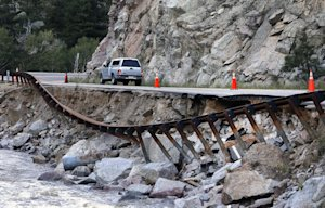 A guardrail hangs away from a closed canyon road, where…