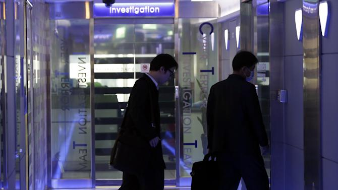 Unidentified men arrive at Cyber Terror Response Center of National Police Agency in Seoul, South Korea, Thursday, March 21, 2013. A Chinese Internet address was the source of a cyberattack on one company hit in a massive network shutdown that affected 32,000 computers at six banks and media companies in South Korea, initial findings indicated Thursday. (AP Photo/Lee Jin-man)