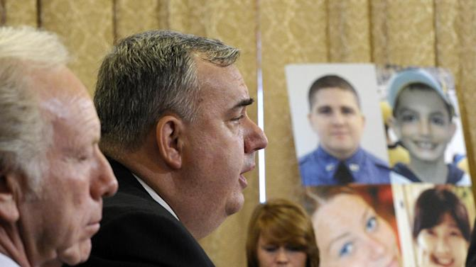 """Boston Police Commissioner Edward Davis testifies before the House Homeland Security Committee at a hearing on """"The Boston Bombings: A First Look,"""" on Capitol Hill in Washington, Thursday, May 9, 2013. Former Sen. Joeseph Lieberman, I-Conn., sits at left, and photos of those who were killed at the Boston Marathon bombing are at right. (AP Photo/Susan Walsh)"""
