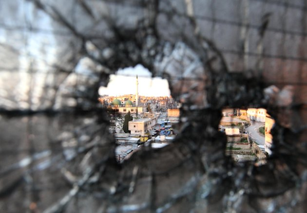 FILE - Bullet holes are seen in a window in Tripoli, Lebanon, Saturday, Feb. 11, 2012. Clashes between pro- and anti-Syria gunmen in the northern Lebanese city of Tripoli left two people dead and 12 w