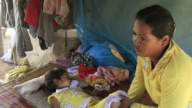 FILE- In this Monday, July 9, 2012, file photo,  Mean Thida, 4, affected with mystery disease, sleeps beside her mother as she receives treatment via a bottle of serum, not in photo, at their home near a dump site at Sambour village, on the outskirts of Phnom Penh, Cambodia. The enterovirus 71 strain, or EV-71, raised fears earlier this week after it was detected in some lab samples taken after 52 of 59 Cambodian children died suddenly from a mystery illness that sparked international alarm. Health officials are still investigating, but say the virus is likely to blame. (AP Photo/Heng Sinith, File)