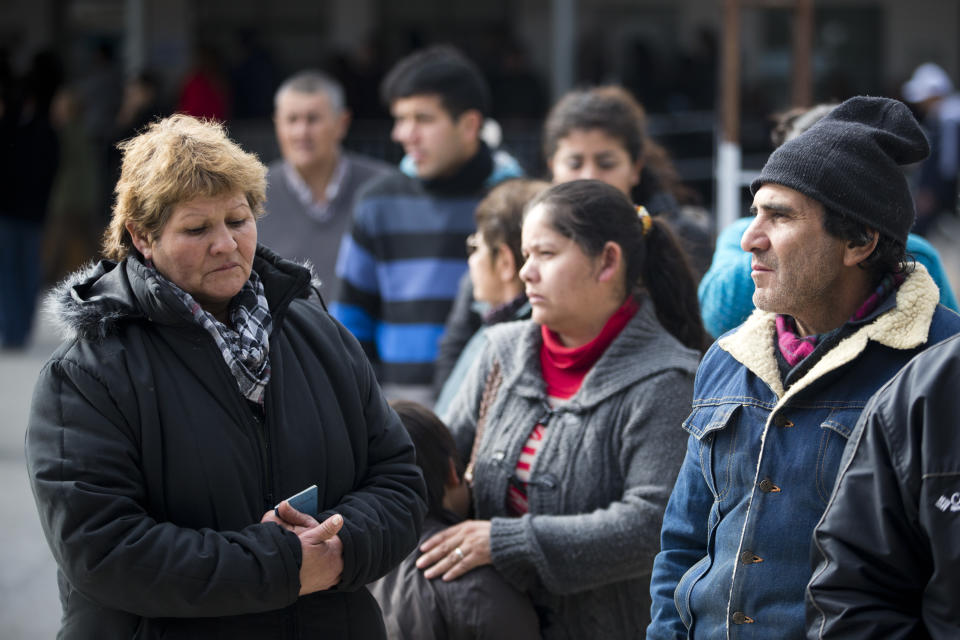 People stand in line to vote in Buenos Aires' Tigre district , Argentina, Sunday, Aug. 11, 2013. Argentines went to the polls in a nationwide mandatory primaries to select candidates for the Oct. 27 midterm election for legislators and senators.(AP Photo/Victor R. Caivano)