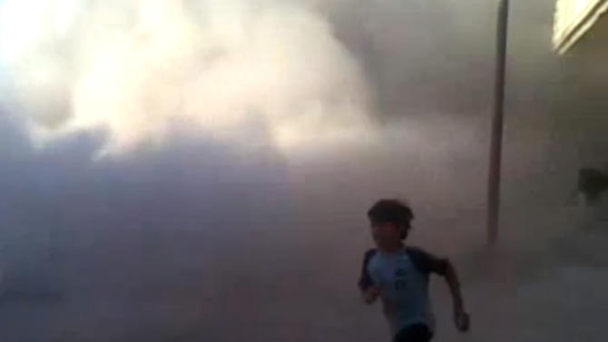 This frame grab made from an amateur video provided by Syrian activists on Monday, May 28, 2012, purports to show the massacre in Houla on May 25 that killed more than 100 people, many of them children. The amateur footage shows people running along a street, purportedly just after the attack on Houla started. (AP Photo/Amateur Video via AP video) THE ASSOCIATED PRESS IS UNABLE TO INDEPENDENTLY VERIFY THE AUTHENTICITY, CONTENT, LOCATION OR DATE OF THIS CITIZEN JOURNALISM IMAGE
