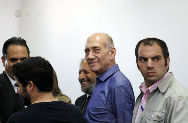 Former Israeli Prime Minister Ehud Olmert stands next to lawyers at Jerusalem's District Court following a verdict hearing in his trial Tuesday, July 10, 2012. An Israeli court on Tuesday cleared Olmert of the major charges in a corruption trial that forced him from power. Olmert was found guilty of a lesser offense, and it was not clear whether that verdict could send him to jail. (AP Photo/Gali Tibbon, Pool)