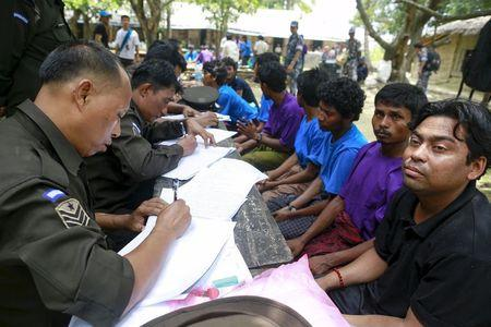 Rohingya Muslims from Myanmar, who were rescued by the Myanmar navy alongside Bangladesh refugees, are interviewed by immigration officers at a Muslim religious school used as a temporary refugee camp, at the Aletankyaw village in the Maungdaw township