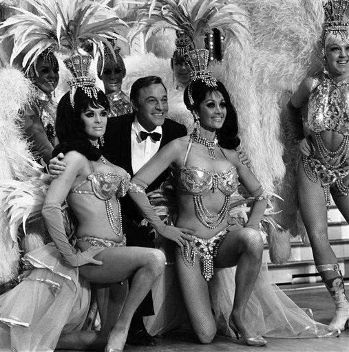 """Actor Gene Kelly is framed by Felicia Atkins, left, and Joyce Grayson, members of the famed Folies Bergere, during rehearsal for his TV special, """"Gene Kelly's Wonderful World of Girls,"""" at the Hotel Tropicana in Las Vegas, April 14, 1959. (AP Photo)"""
