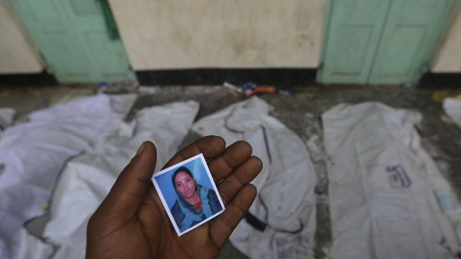 A Bangladeshi relative holds a picture as he searches for a missing loved one at a makeshift morgue in a schoolyard near a building that collapsed Wednesday in Savar, near Dhaka, Bangladesh, Saturday, April 27, 2013. Police in Bangladesh arrested two owners of a garment factory in a shoddily-constructed building that collapsed this week, killing hundreds of people, as protests spread to a second city Saturday with hundreds of people throwing stones and setting fire to vehicles. (AP Photo/Kevin Frayer)