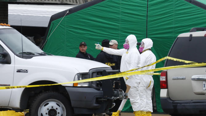 Federal authorities in hazmat suits stand outside a small retail space where neighboring business owners said Everett Dutschke used to operate a martial arts studio, Wednesday, April 24, 2013 in Tupelo, Miss., in connection with the recent ricin attacks. No charges have been filed against Dutschke and he hasn't been arrested. (AP Photo/Rogelio V. Solis)