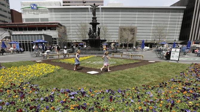 This April 10, 2013 photo shows Hannah Bailey, left, running the bases with sister Eva Bailey on a baseball diamond floral display set up on Fountain Square in Cincinnati. The heart of downtown Cincinnati, Fountain Square underwent a $49 million renovation and reopened in 2006. (AP Photo/Al Behrman)