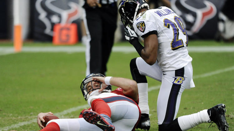 Baltimore Ravens cornerback Cary Williams (29) kneels over Houston Texans quarterback Matt Schaub, left, after sacking him during the third quarter of an NFL football game, Sunday, Oct. 21, 2012, in Houston. (AP Photo/Dave Einsel)