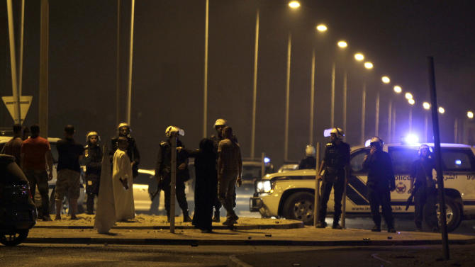 "Riot police keep villagers back from the site where a Bahraini youth was killed during an anti-government protest, allegedly by police shotgun fire, in the western village of Sadad, Bahrain, early Saturday, Sept. 29, 2012. An Interior Ministry statement said a police patrol was attacked with petrol bombs and iron rods, and one person died when ""policemen defended themselves."" A witness among protesters said demonstrators were marching against the government when a policeman suddenly stepped out near the youth and shot him at close range. (AP Photo/Hasan Jamali)"