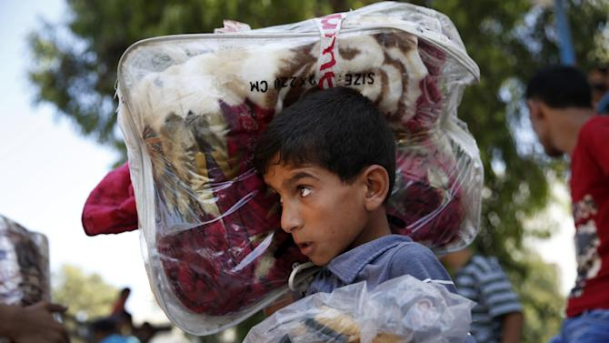 A Palestinian youth carries blankets donated to the United Nations school where hundreds of families sought refuge after fleeing their homes due to heavy Israeli missile strikes in Gaza City, Wednesday, July 23, 2014. Hundreds of thousands of Palestinians have fled their homes and are staying in 77 UN shelters, according to UNRWA, the U.N. refugee agency for Palestinians. The number of people who have been forced to seek shelter has increased nearly six-fold since the start of Israel's ground operation. (AP Photo/Lefteris Pitarakis)