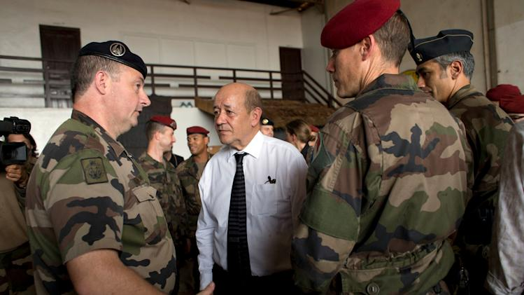 FILE - This Thursday, Jan. 2, 2014, file photo shows French Defense Minister Jean-Yves Le Drian talking with French soldiers from Operation Sangaris, at Mpoko Camp in Bangui, Central African Republic. France will broaden its military presence in Africa's turbulent Sahel region with specialized new outposts to better fight the terror threat from extremist groups such as al-Qaida, the defense minister said Tuesday. In an exclusive interview with The Associated Press, Jean-Yves Le Drian said France is moving toward a regional counterterrorism approach in former French colonies such as Chad, Ivory Coast, Burkina Faso, Niger and Mali. (AP Photo/Rebecca Blackwell, File)