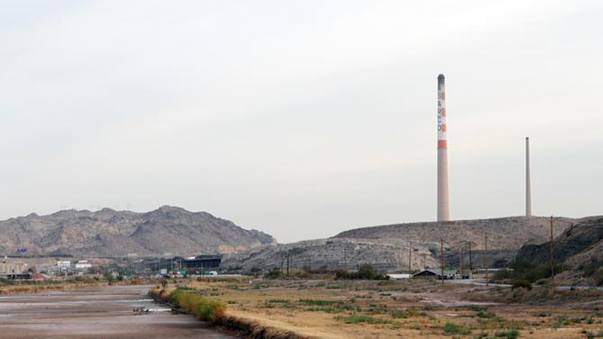 This Wednesday, Nov. 28, 2012 photo shows ASARCO copper smelter smokestacks near the Rio Grande in El Paso, Texas. People spent years trying to close the massive copper plant they said spewed fumes that made their eyes teary, their lungs burn. Now, more than a decade after they claimed victory when the copper smelter shut down, some who opposed the plant are banding together in a long-shot effort to prevent the demolition of the plant's smokestacks that have dominated the local skyline for nearly half a century. (AP Photo/Juan Carlos Llorca)