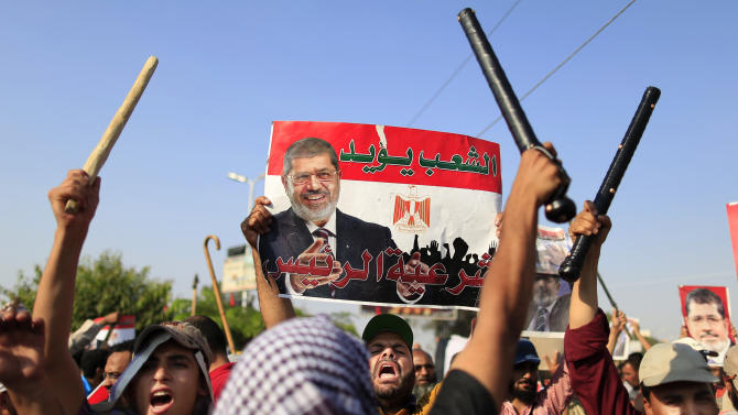 """Supporters of Egypt's Islamist President Mohammed Morsi chant slogans during a rally in Nasser City, Cairo, Thursday, July 4, 2013. The chief justice of Egypt's Supreme Constitutional Court was sworn in Thursday as the nation's interim president, taking over hours after the military ousted the Islamist President Mohammed Morsi. Adly Mansour took the oath of office at the Nile-side Constitutional Court in a ceremony broadcast live on state television. According to military decree, Mansour will serve as Egypt's interim leader until a new president is elected. A date for that vote has yet to be set. Arabic reads, """"the people support legitimacy for the president,"""". (AP Photo/Hassan Ammar)"""