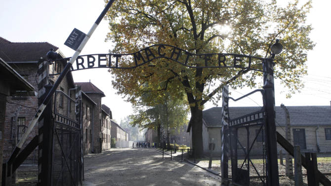 """FILE - In this Oct. 19, 2012 file photo the entrance with the inscription """"Arbeit Macht Frei"""" (Work Sets You Free) gate of the former German Nazi death camp of Auschwitz is pictured at the Auschwitz-Birkenau memorial in Oswiecim, Poland. A 94-year-old man, deported from the U.S. for lying about his Nazi past, is unfit for trial on allegations he was an accessory to thousands of murders as an SS guard at Auschwitz, a German court said Friday, Feb. 28, 2014. The Ellwangen state court said Hans Lipschis is suffering from """"worsening dementia"""" and could not be tried. He was charged with 10,510 counts of accessory to murder on allegations he served as a guard at the death camp from 1941 to 1943. (AP Photo/Czarek Sokolowski, File)"""
