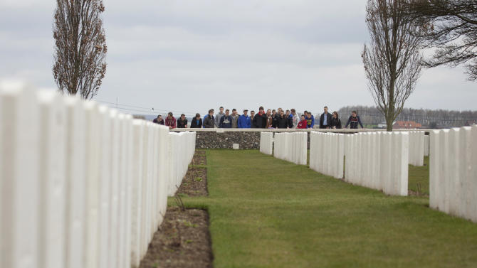 A group of school children look over a stone fence toward a row of WWI graves at Tyne Cot cemetery in Zonnebeke, Belgium on Monday, April 15, 2013. With nearly 12,000 graves the cemetery is the largest Commonwealth war cemetery in the world in terms of burials. Currently renovation work is being done on the cemetery in preparation for centenary events which begin in 2014. (AP Photo/Virginia Mayo)