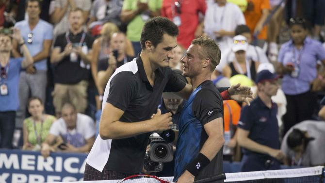 Hewitt of Australia embraces compatriot Tomic after Tomic defeated him in their second round match at the U.S. Open Championships tennis tournament in New York