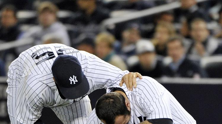 New York Yankees' Mark Teixeira, left, checks on relief pitcher Joba Chamberlain after Chamberlain was hit by a broken bat during the twelfth inning of Game 4 of the American League division baseball series against the Baltimore Orioles, Thursday, Oct. 11, 2012, in New York. (AP Photo/Bill Kostroun)