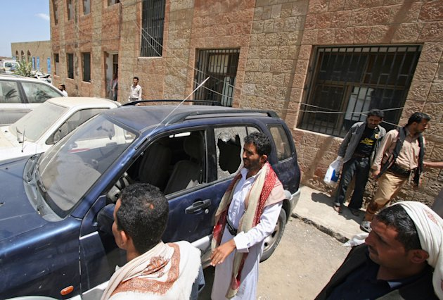 Yemenis gather around a damaged vehicle purported to belong to an American teacher shot by gunmen in Taiz, Yemen, Sunday, March 18, 2012. Two gunmen on a motorcycle shot dead early Sunday an American